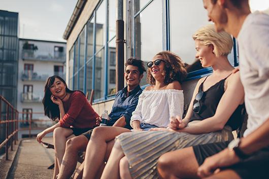 Junge Leute sitzen in einer Gruppe auf dem Balkon, lachen und diskutieren.