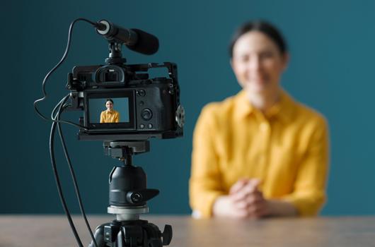 Junge Frau sitzt vor einer Videokamera