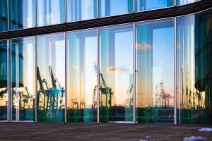 Hamburger Hafenkräne spiegeln sich im Fenster