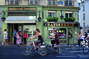 Junge Menschen fahren mit Fahrrädern durch Paris