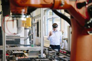 Ingenieur arbeitet mit einer HoloLens: Platzieren Sie einen virtuellen Roboterarm in der Produktionslinie