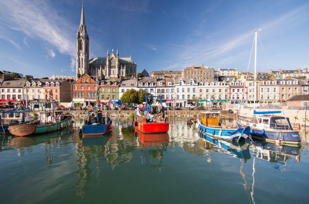 Die dominierende Form der St. Colman's Cathedral erhebt sich über die Terrassenstraßen und bunten Fischerboote der kleinen Touristenstadt Cobh am Hafen von Cork.